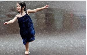 Nena ballant sota la pluja